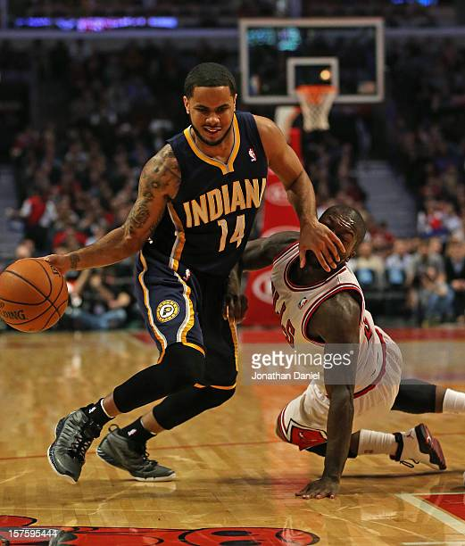 J Augustin of the Indiana Pacers fouls Nate Robinson of the Chicago Bulls as he tries to drive to the lane at the United Center on December 4 2012 in...
