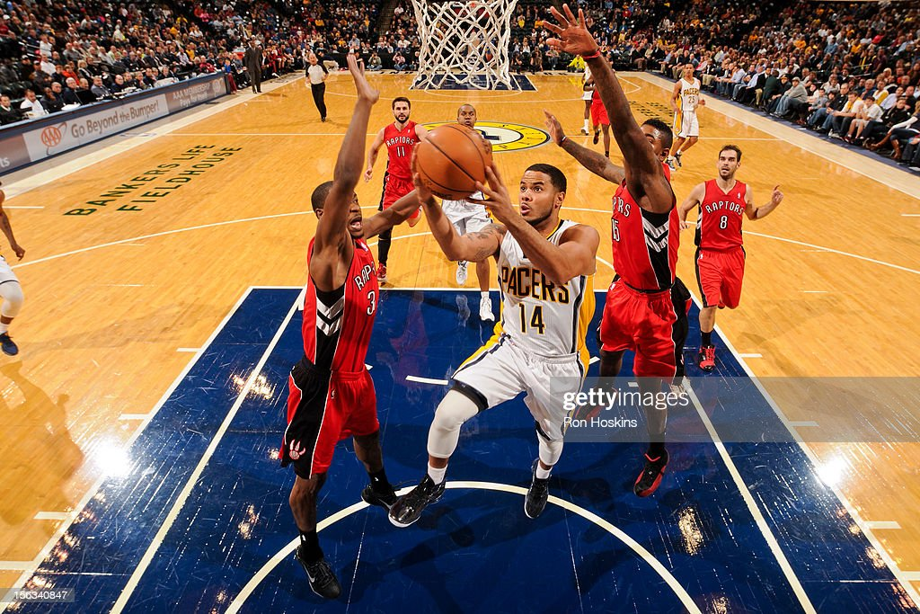 D.J. Augustin #14 of the Indiana Pacers goes to the basket against Amir Johnson #15 and Terrence Ross #31 of the Toronto Raptorson November 13, 2012 at Bankers Life Fieldhouse in Indianapolis, Indiana.