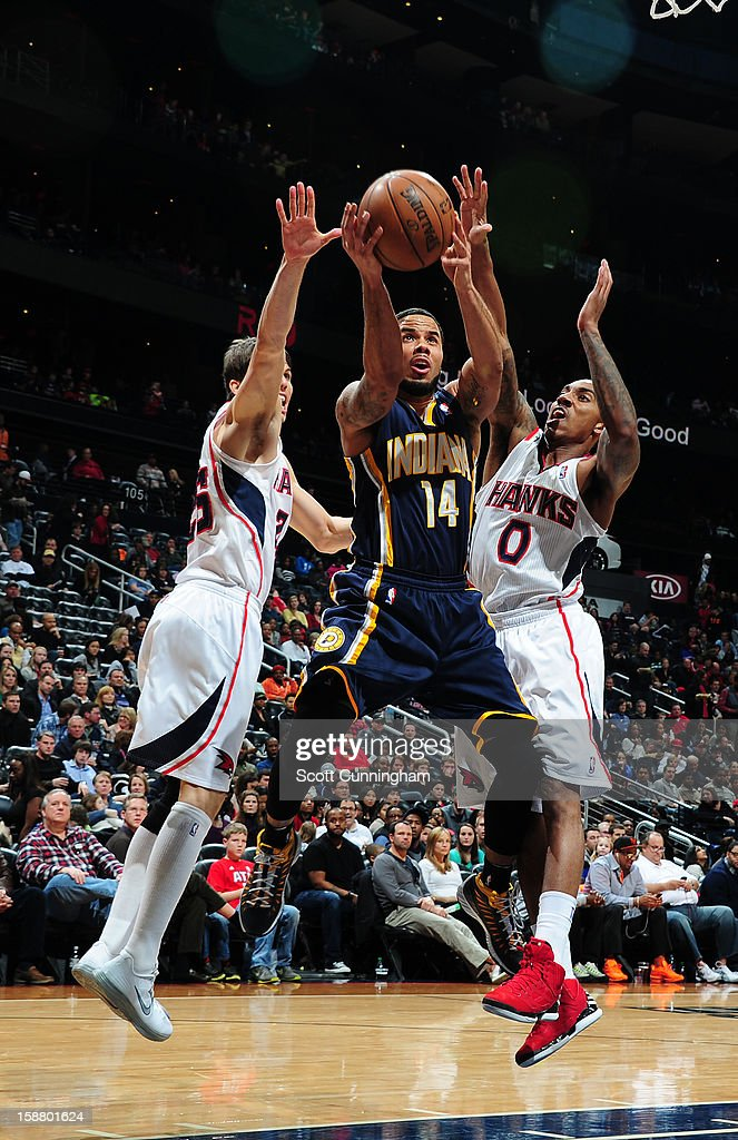 D.J. Augustin #14 of the Indiana Pacers goes to the basket against Kyle Korver #26 and Jeff Teague #0 of the Atlanta Hawks on December 29, 2012 at Philips Arena in Atlanta, Georgia.