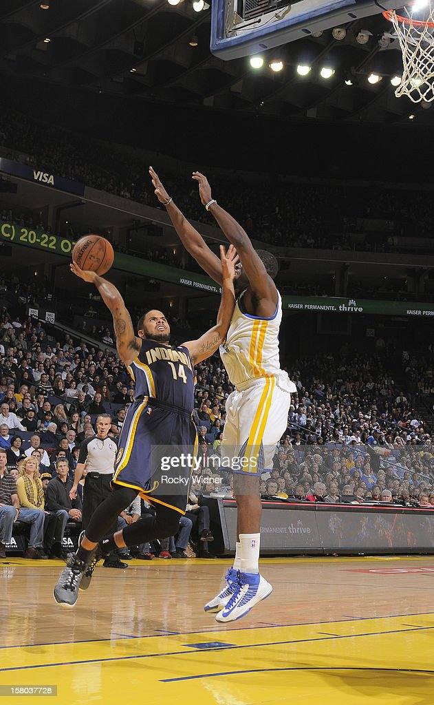 D.J. Augustin #14 of the Indiana Pacers goes up for the shot against Draymond Green #23 of the Golden State Warriors on December 1, 2012 at Oracle Arena in Oakland, California.