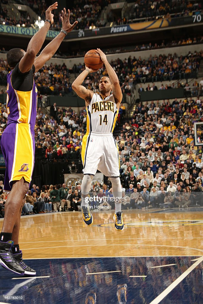 D.J. Augustin #14 of the Indiana Pacers shoots a jumper against Dwight Howard #12 of the Los Angeles Lakers on March 15, 2013 at Bankers Life Fieldhouse in Indianapolis, Indiana.