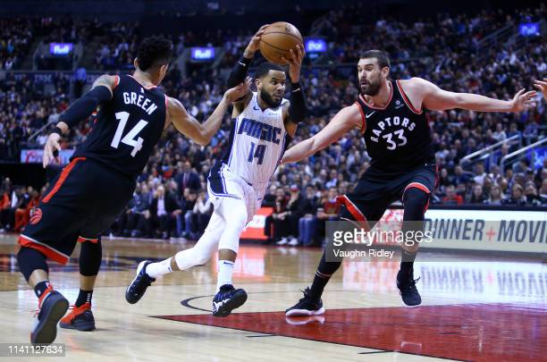 J Augustin of the Orlando Magic dribbles the ball as Danny Green and Marc Gasol of the Toronto Raptors defend during the first half of an NBA game at...