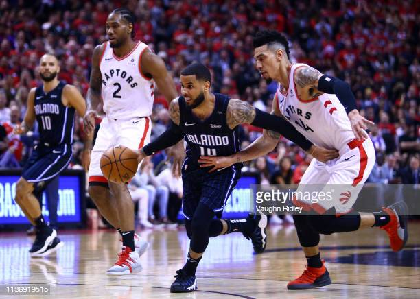J Augustin of the Orlando Magic dribbles the ball as Danny Green of the Toronto Raptors defends during Game One of the first round of the NBA...