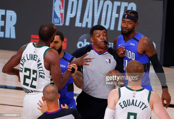 Augustin of the Orlando Magic holds back Khris Middleton of the Milwaukee Bucks and referee Tony Brothers holds back Terrence Ross of the Orlando...