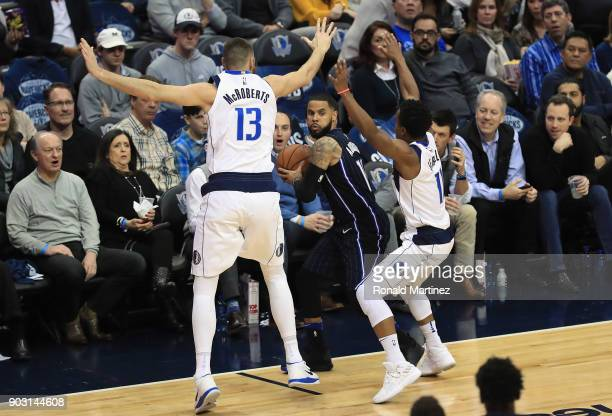 J Augustin of the Orlando Magic looks to pass against Josh McRoberts and Yogi Ferrell of the Dallas Mavericks in the first half at American Airlines...