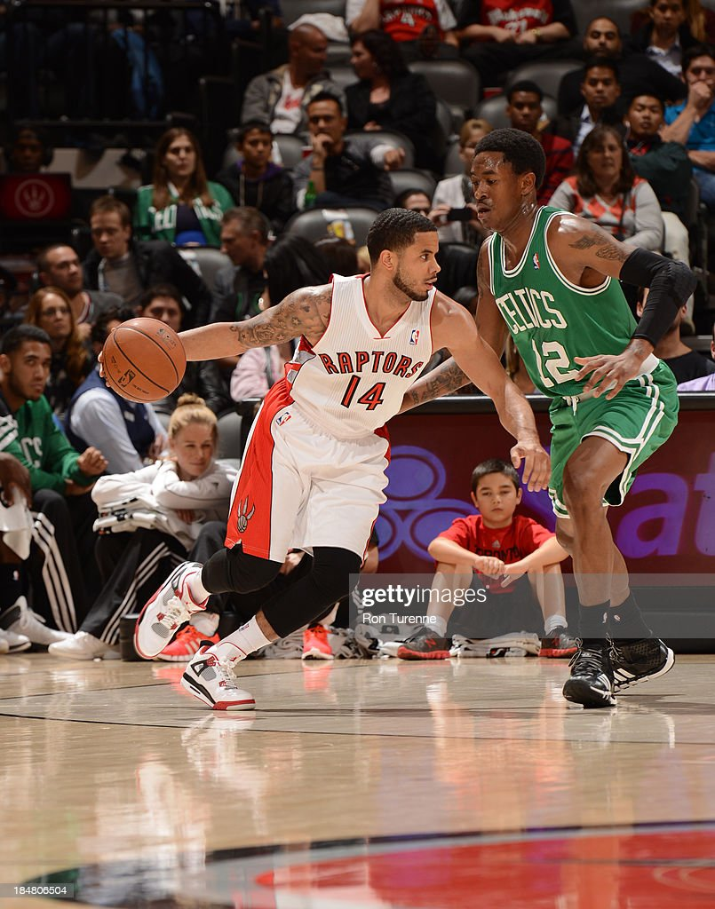 D.J. Augustin #14 of the Toronto Raptors drives against MarShon Brooks #12 of the Boston Celtics during the game on October 16, 2013 at the Air Canada Centre in Toronto, Ontario, Canada.