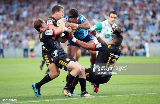 Augustine Pulu of the Blues forces his way over the line in the tackle from the Chiefs defence during the round two Super Rugby match between the...