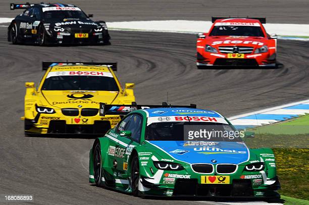 Augusto Farfus of Brazil and BMW Team RBM drives infront of Timo Glock of Germany and BMW Team MTEK Daniel Juncadella of Spain and stern Mercedes AMG...