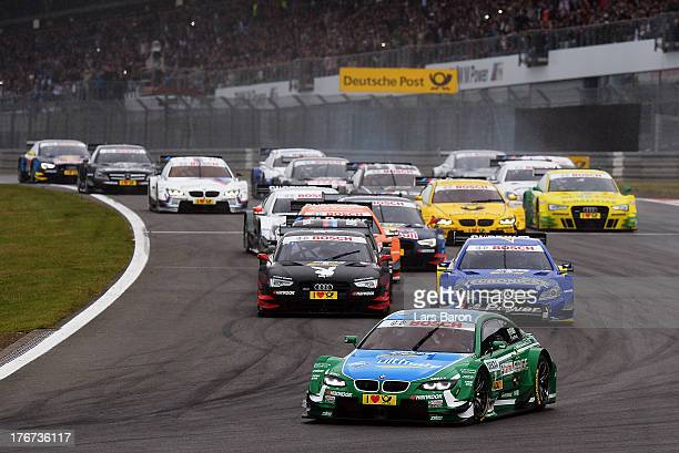 Augusto Farfus of Brazil and BMW Team RBM leads the pack into the first corner during the seventh round of the DTM 2013 German Touring Car...