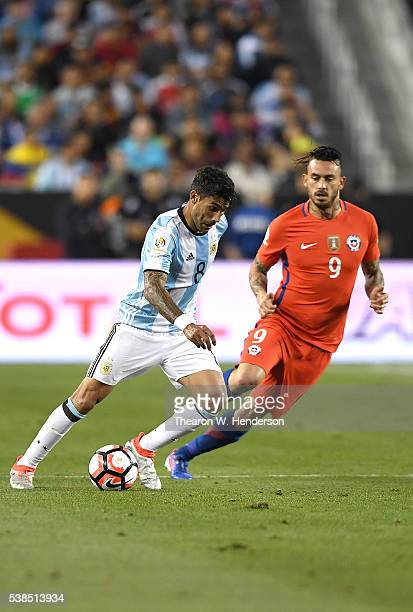 Augusto Fernandez of Argentina dribbles the ball away from Mauricio Pinilla of Chile during the 2016 Copa America Centenario Group match play between...
