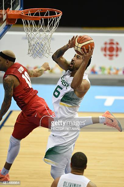 Augusto Lima of Brazil drives to the basket against Elias Ayuso of Puerto Rico during the Basketball men's preliminary round at the 2015 Pan American...