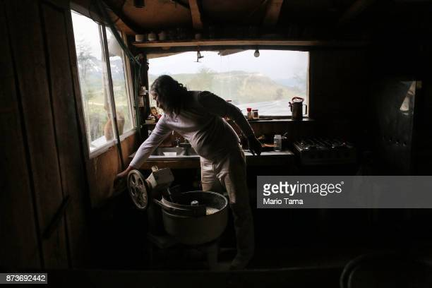 Augusto prepares dough for empanadas in his home built in an informal mountainside community whose residents depend on runoff water from the receding...