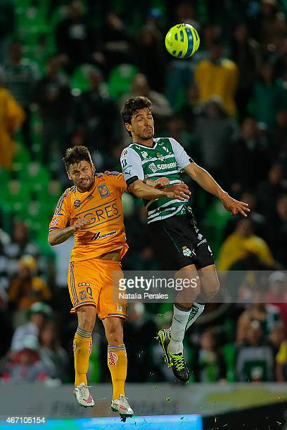 Augusto Sobis of Tigres jumps for the ball with Oswaldo Alanis of Santos during a match between Santos Laguna and Tigres UANL as part of 11th round...