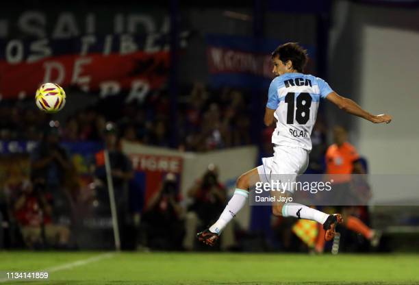 Augusto Solari of Racing Club kicks the ball to score the first goal of his team during a match between Tigre and Racing Club as part of Superliga...