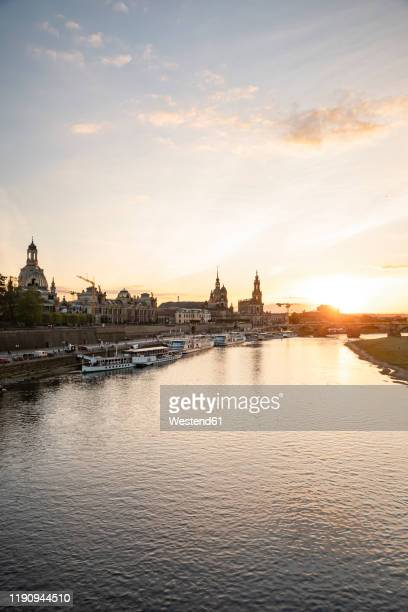 augustus bridge over elbe river against sky in city during sunset, saxony, germany - dresden stock-fotos und bilder