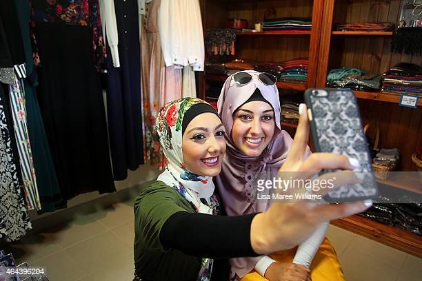 Aula Dbouk and Eman Elnachar take a photograph at Sara Elmir's home clothing studio on December 4 2014 in Bankstown Australia Sara Elmir 26 and...