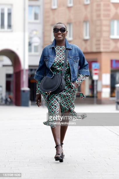 Auma Obama wearing a brown and mint green midi length longsleeve dress with abstract floral pattern and tied waist by Odeeh, a blue denim jeans...