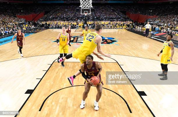 Aundre Jackson of the Loyola Ramblers pump fakes Duncan Robinson of the Michigan Wolverines during the 2018 NCAA Men's Final Four semifinal game at...