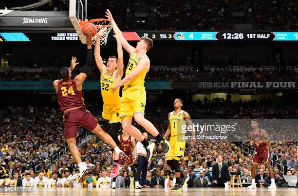 Aundre Jackson of the Loyola Ramblers shoots the ball during the first half against Duncan Robinson and Jon Teske of the Michigan Wolverines in the...