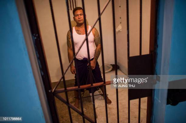 Aung Soe a former prisoner demonstrates how he was shackled while inside a prison cell during an exhibition to commemorate the 30th anniversary of...