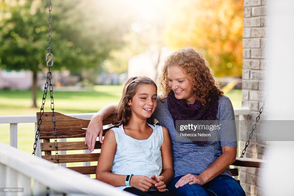 Aunt and niece sitting on porch swing, smiling : Stock Photo