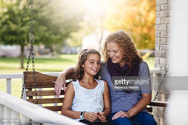 aunt and niece sitting on porch swing, smiling - aunt fotografías e imágenes de stock