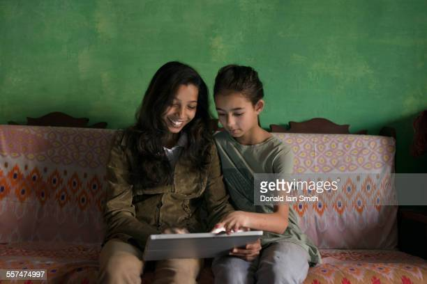 aunt and niece using digital tablet on sofa - punjab pakistan stock pictures, royalty-free photos & images