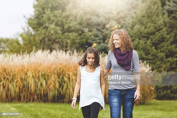 aunt and niece walking together in garden - aunt stock pictures, royalty-free photos & images
