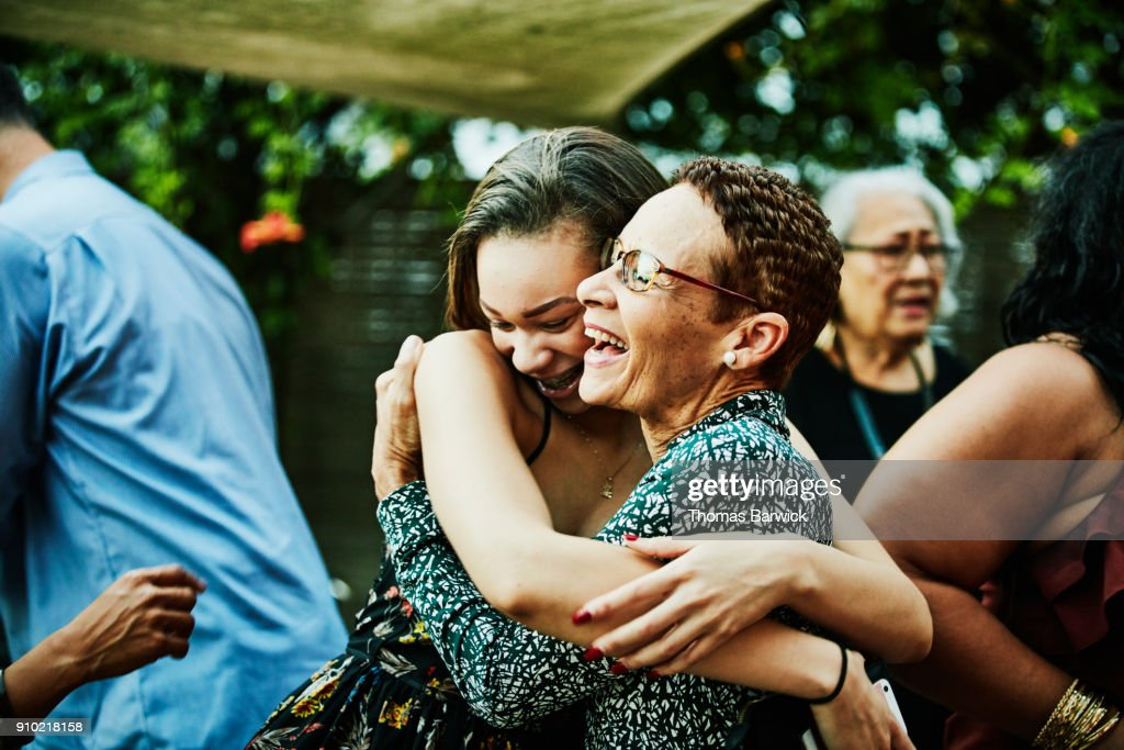 Aunt embracing niece after outdoor family dinner party : Stock Photo
