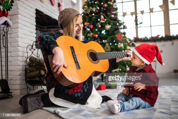 aunt playing guitar to her nephew - zia e nipote foto e immagini stock