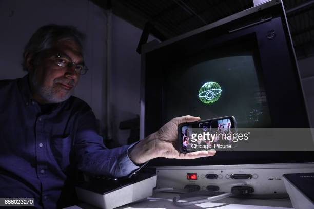 Aura Technologies President Steve Heminover holds a phone with a scene from the original Star Wars beside an image of the Death Star on the computer...