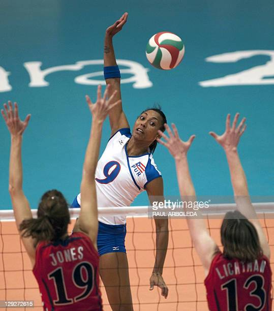 Aurea Cruz of Puerto Rico spikes the ball over Jessica Jones and Cassidy Lichtman of the Unites States in the Women's Volleyball Pool B Preliminary...