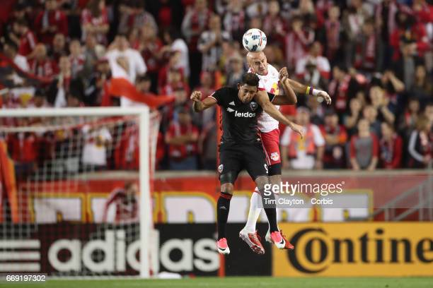 Aurelien Collin of New York Red Bulls heads clear while challenged by Jose Guillermo Ortiz of DC United during the New York Red Bulls Vs DC United...