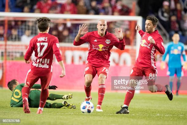 Aurelien Collin of New York Red Bulls reacts watched by team meats Ben Mines of New York Red Bulls and Vincent Bezecourt of New York Red Bulls during...