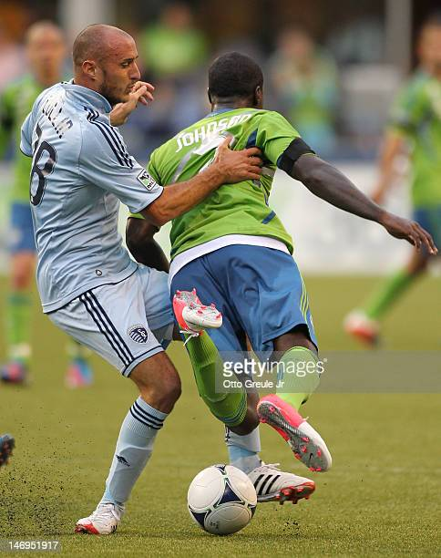 Aurelien Collin of Sporting Kansas City battles Eddie Johnson of the Seattle Sounders at CenturyLink Field on June 20 2012 in Seattle Washington The...