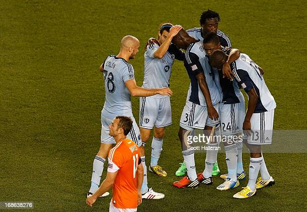 Aurelien Collin of Sporting Kansas City celebrates with his teammates after defeating the Dynamo 10 as Brad Davis of the Houston Dynamo walks off the...