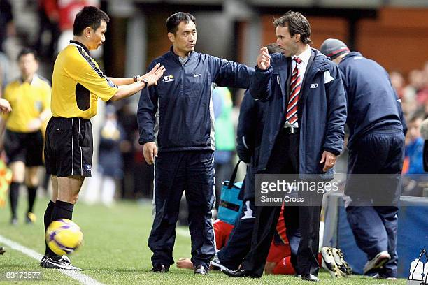 Aurelio Vidmar of United is pushed back by the referees during the AFC Champions League semifinal first leg match between Adelaide United and...
