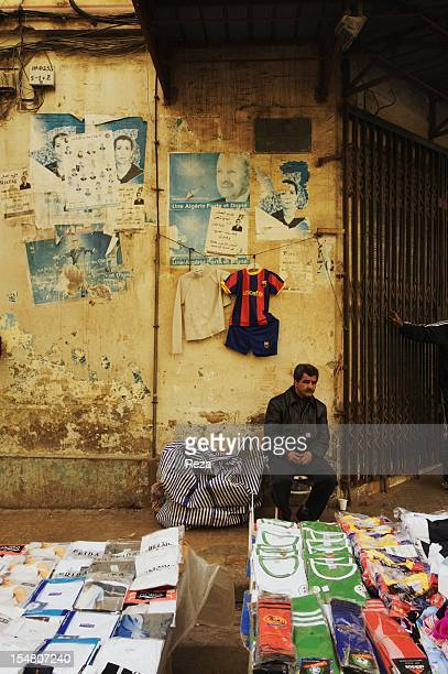 Aures road or the ancient bastille road on April 8 in Oran Algeria Hebdomadaire market A merchant in front of his sports tshirt stand One the wall...