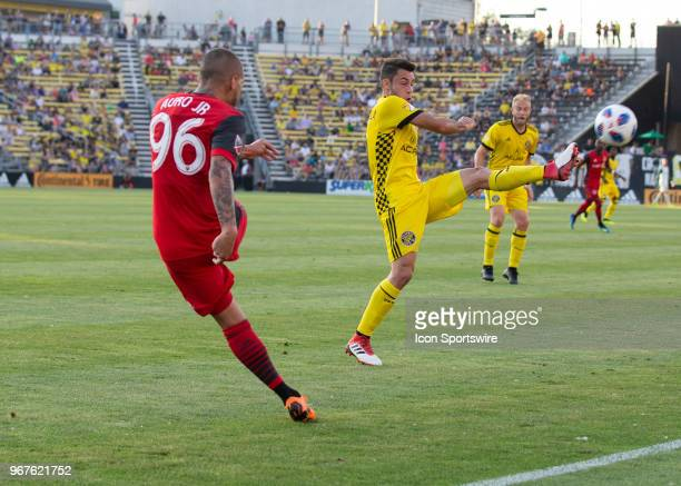 Auro of Toronto FCclears the ball past Milton Valenzuela of Columbus Crew SC during the game between the Columbus Crew SC and the Toronto FC at...