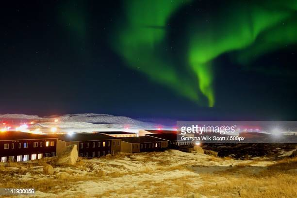 aurora blooming over a city - nunavut stock pictures, royalty-free photos & images