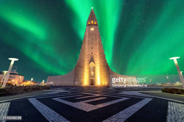 aurora borealis above hallgrimskirkja church in central of reykjavik city capital city in iceland - reykjavik stock pictures, royalty-free photos & images