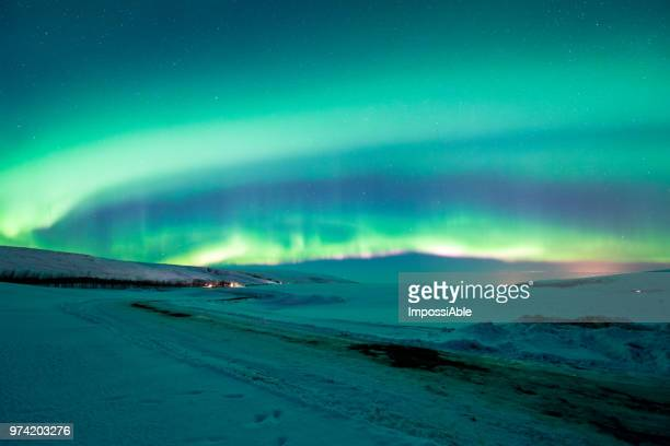 aurora borealis bright and strong in the night sky over snow field in winter iceland - solar flare stock pictures, royalty-free photos & images