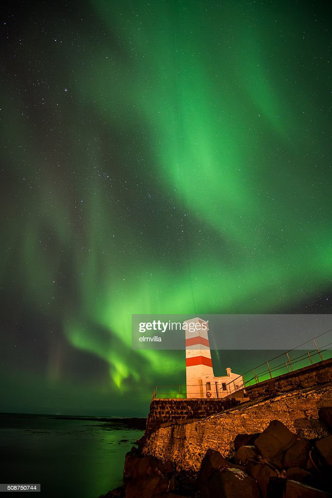 Aurora Borealis in a Winter sky over a lighthouse in Iceland : Stock Photo