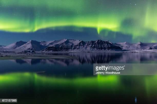 Aurora Borealis in night sky over landscape