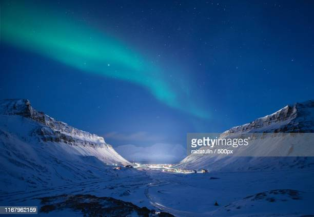 aurora borealis in sky at night above mountains in winter - natuurlijk fenomeen stockfoto's en -beelden