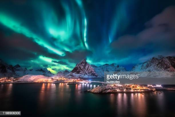 aurora borealis. lofoten islands, norway. aurora. green northern lights. starry sky with polar lights. night winter landscape with aurora, sea with sky reflection and snowy mountains. - aurora borealis stock pictures, royalty-free photos & images