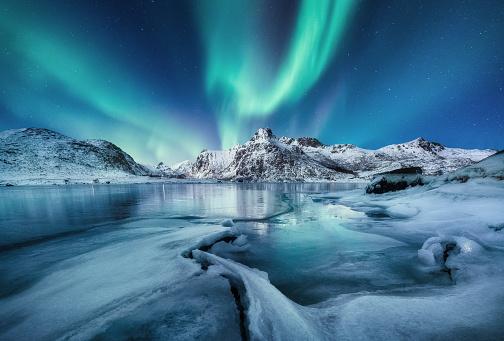 Aurora Borealis, Lofoten islands, Norway. Mountains and frozen ocean. Winter landscape in the night time. Northen light - image 1179753622