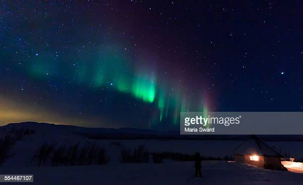 Aurora borealis over a cabin, Swedish Lapland