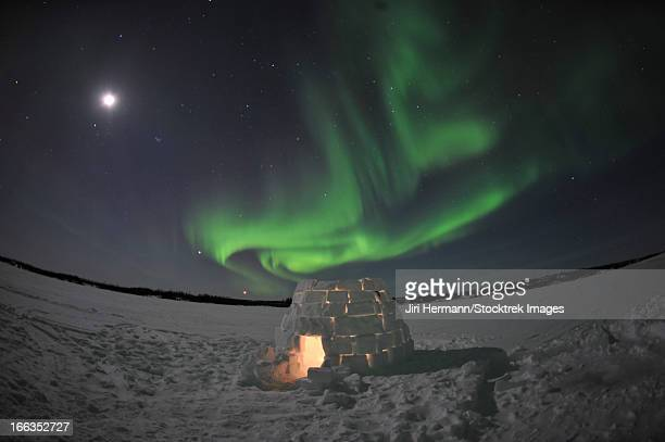 Aurora borealis over an igloo on Walsh Lake, Yellowknife, Northwest Territories, Canada.