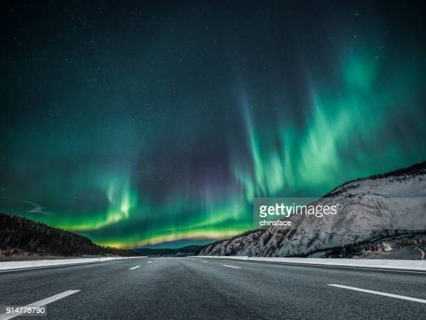 aurora borealis over asphalt road in canada - aurora borealis stock pictures, royalty-free photos & images